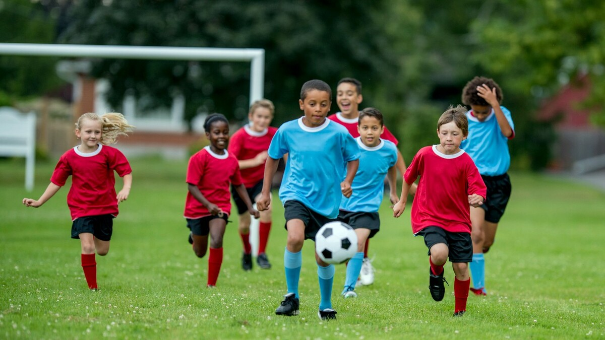 A multi-ethnic group of children are playing soccer